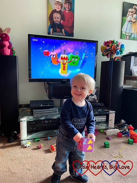Thomas standing in front of the TV with Numberblocks on