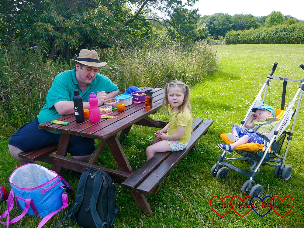Daddy and Sophie sitting on a bench having a picnic while Thomas naps in his buggy