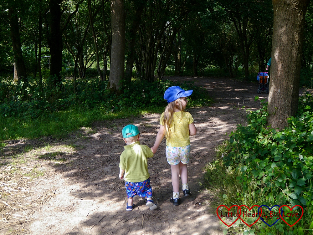 Sophie and Thomas walking hand-in-hand through the woods