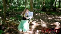 Jessica wearing a fairy costume in the woods, facing away from the camera
