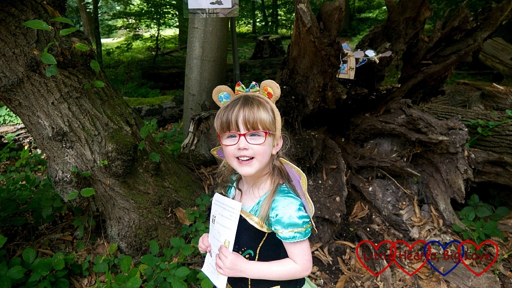 Jessica wearing teddy bear ears, a princess dress and fairy wings out in the woods, lookinga at the camera and smiling