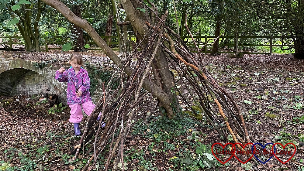 Sophie adding sticks to her den