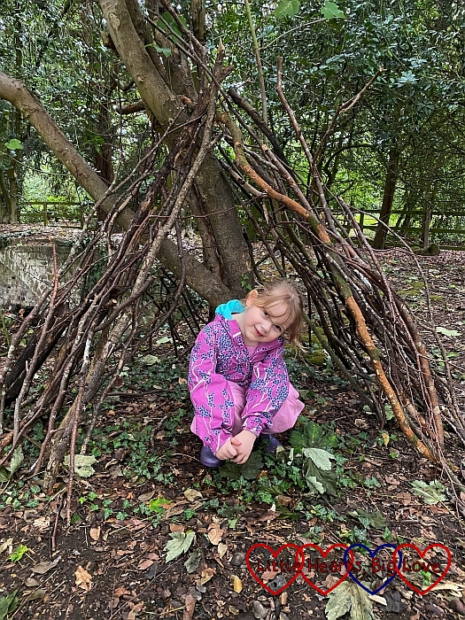 Sophie crouched down inside her finished den