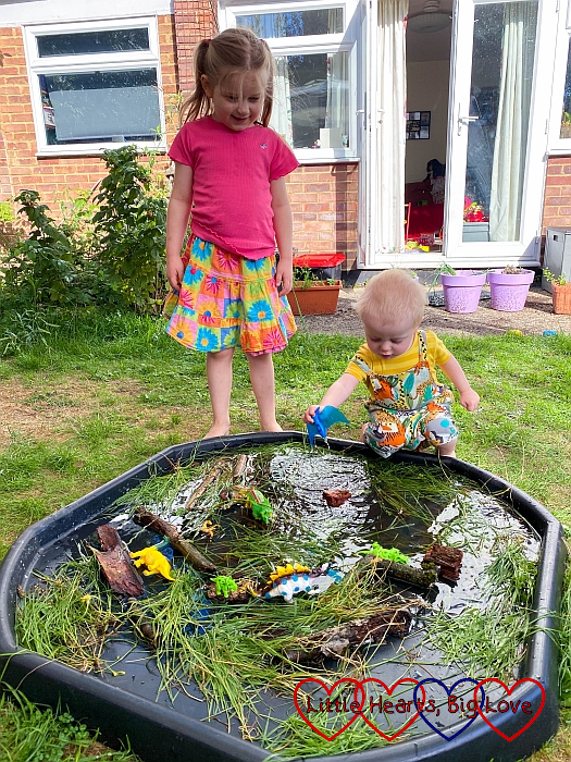 Thomas playing with his dinosaur in the 'dinosaur swamp' tuff tray with Sophie looking on