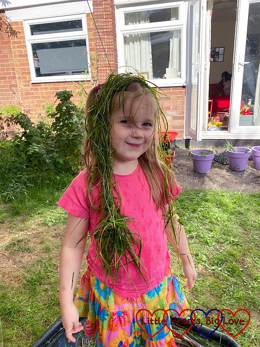 Sophie with long wet grass on her head making a long plait