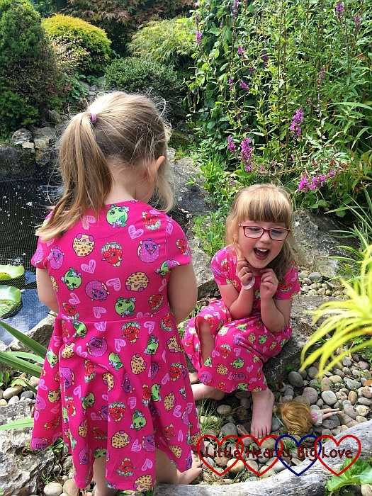 Sophie facing a laughing Jessica who is sitting by a pond