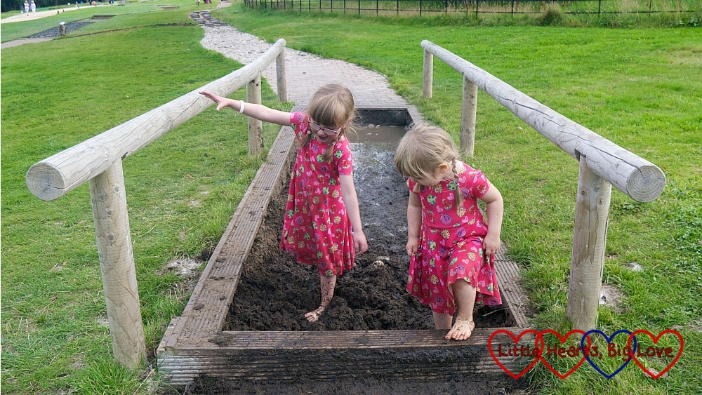 Sophie and Jessica having fun walking barefoot through mud on a sensory trail