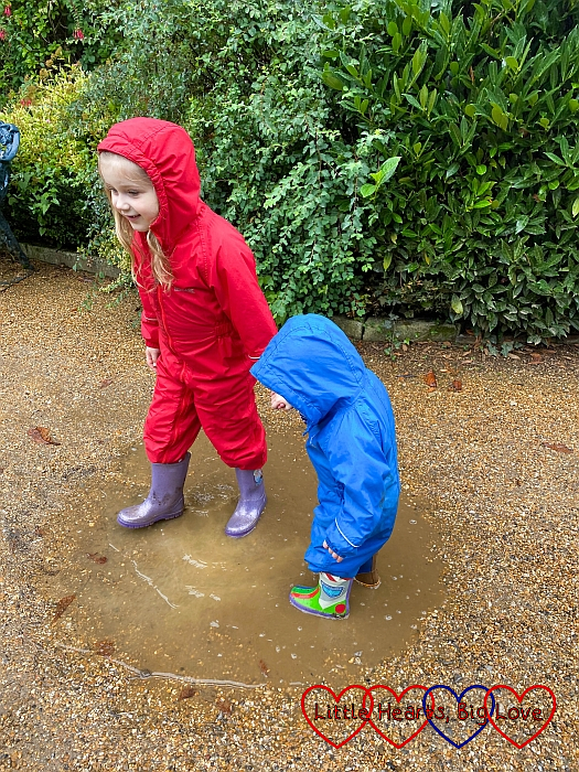Sophie and Thomas splashing in a puddle