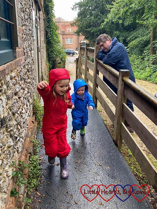 Sophie and Thomas running down the ramp outside the ice house at Hughenden with Daddy looking on