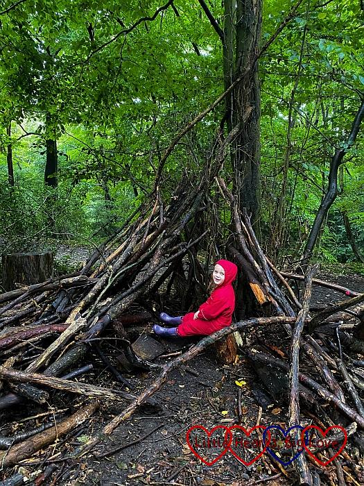 Sophie sitting in a den in the woods at Hughenden