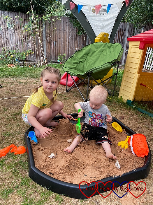 Sophie and Thomas playing in sand in the tuff tray