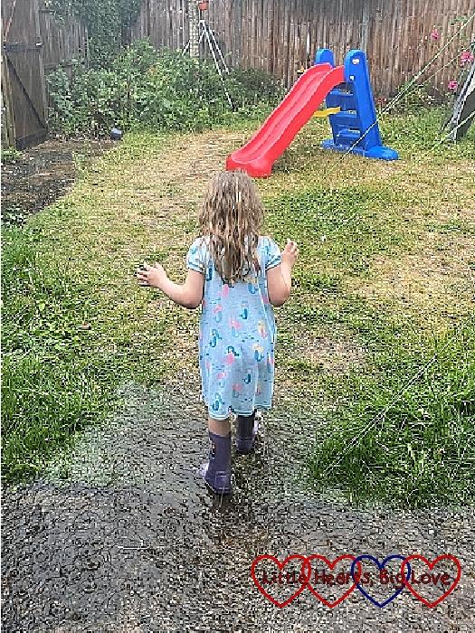 Sophie splashing in puddles in the garden in the rain