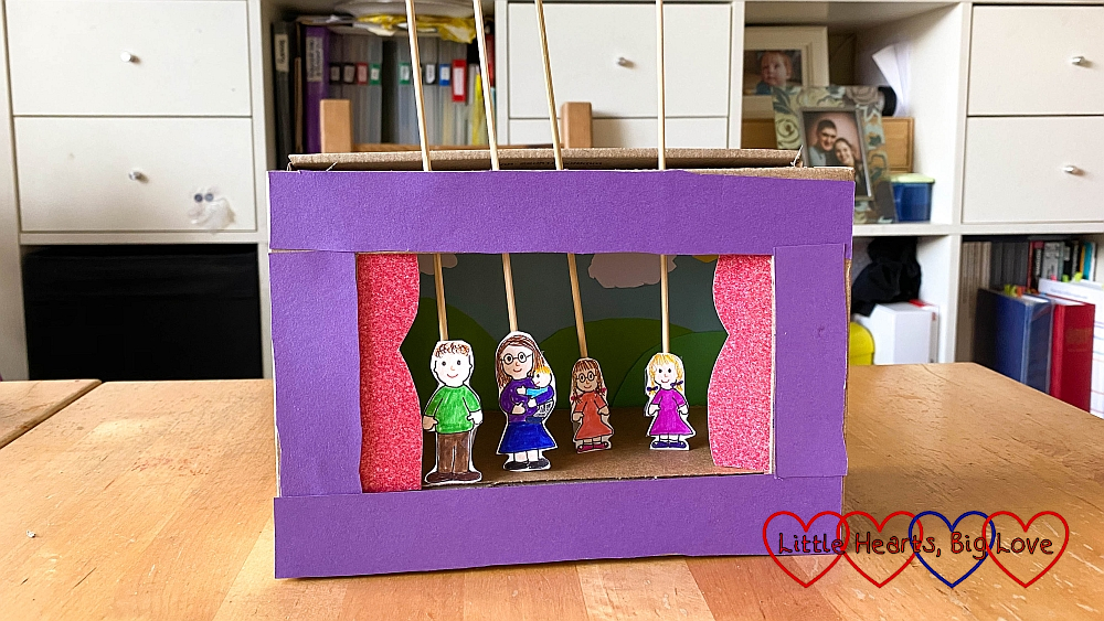 Sophie's shoebox theatre with cartoon figures of me holding Thomas, hubby, Jessica and Sophie stuck to wooden skewers