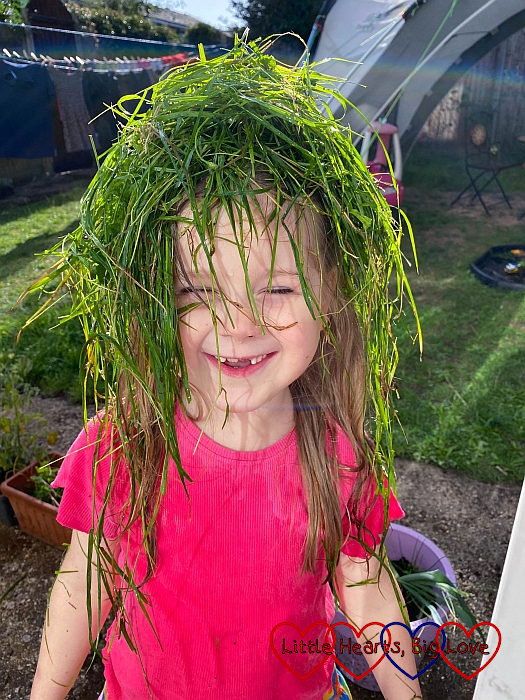 Sophie with a handful of long wet grass on her head
