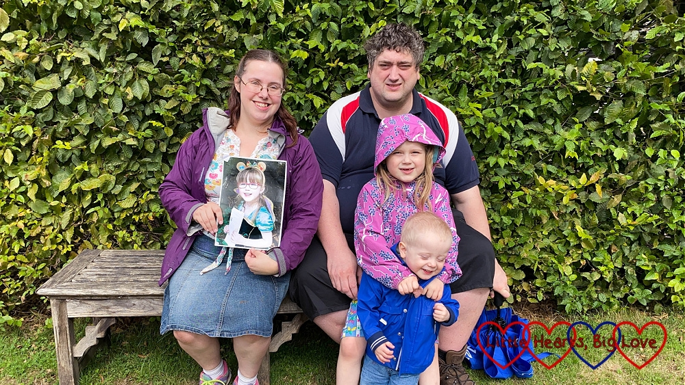 Me (holding a photo of Jessica), hubby, Sophie and Thomas sitting on a bench together