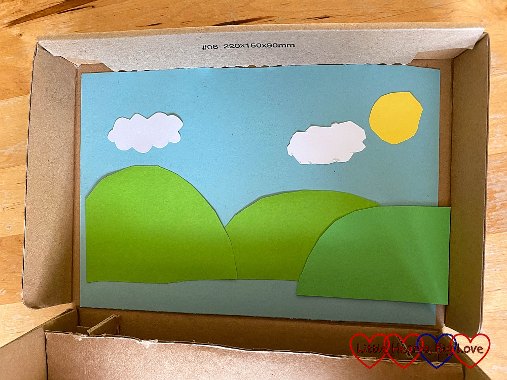 Scenery cut out of coloured card inside the lid of the shoebox