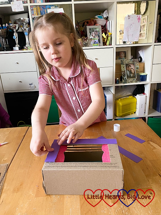 Sophie sticking strips of coloured card to the front of the shoebox