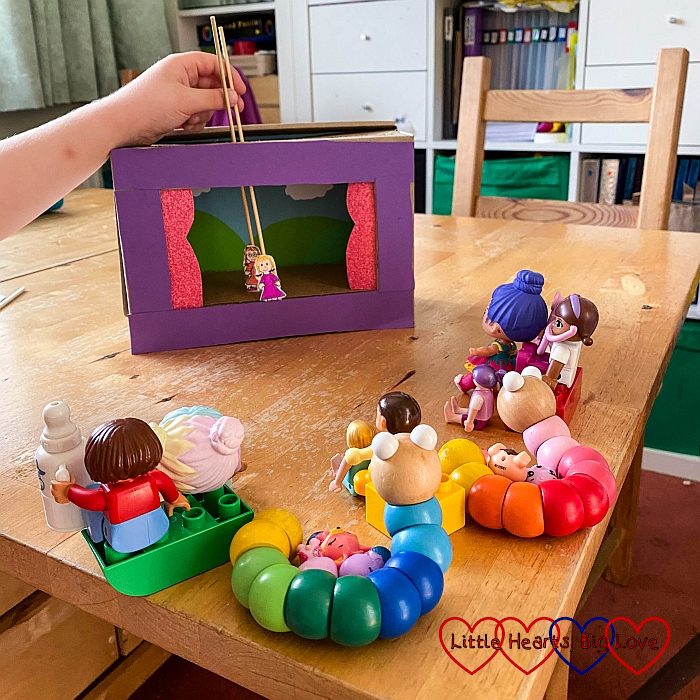 Sophie putting on a show in her shoe box theatre with small toys making up the audience