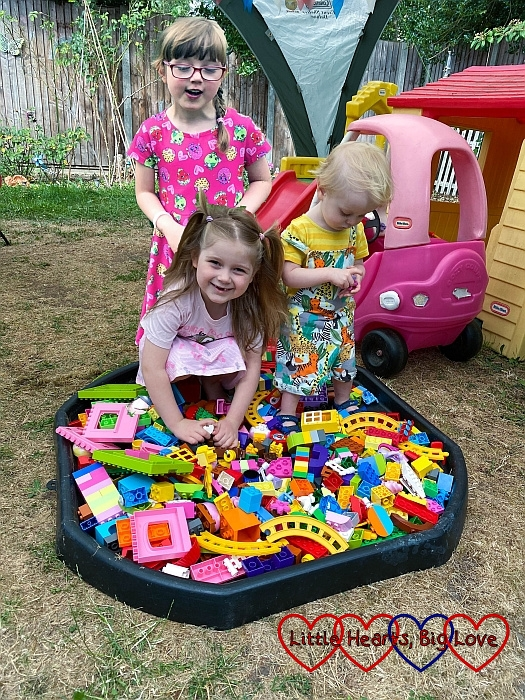 Sophie and Thomas playing with Duplo in the tuff tray with Jessica standing behind them looking down