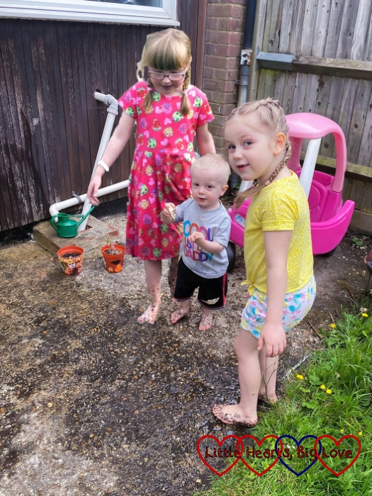 Jessica, Thomas and Sophie splashing barefoot in a muddy puddle