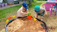 Thomas and Sophie playing with sand in the tuff tray