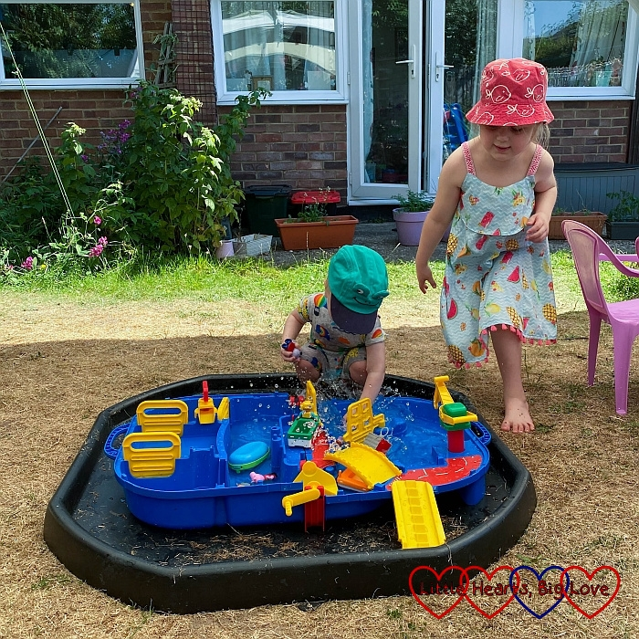 Thomas playng with his AquaPlay lock box in the garden with Sophie next to him