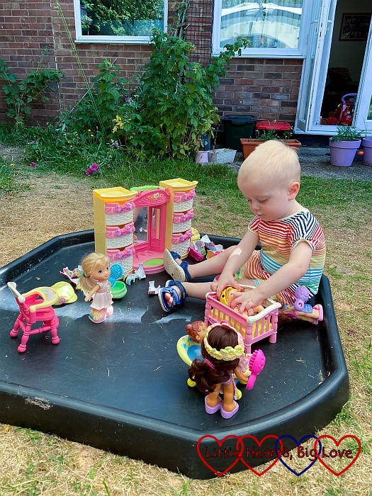 Thomas playing with dress-up dolls in the tuff tray