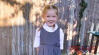 Sophie in a white school polo top and a grey pinafore dress