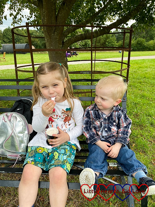 Sophie and Thomas sitting on a bench; Sophie is eating some ice-cream while Thomas looks on