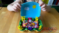 A teddy bears' picnic scene in an egg box