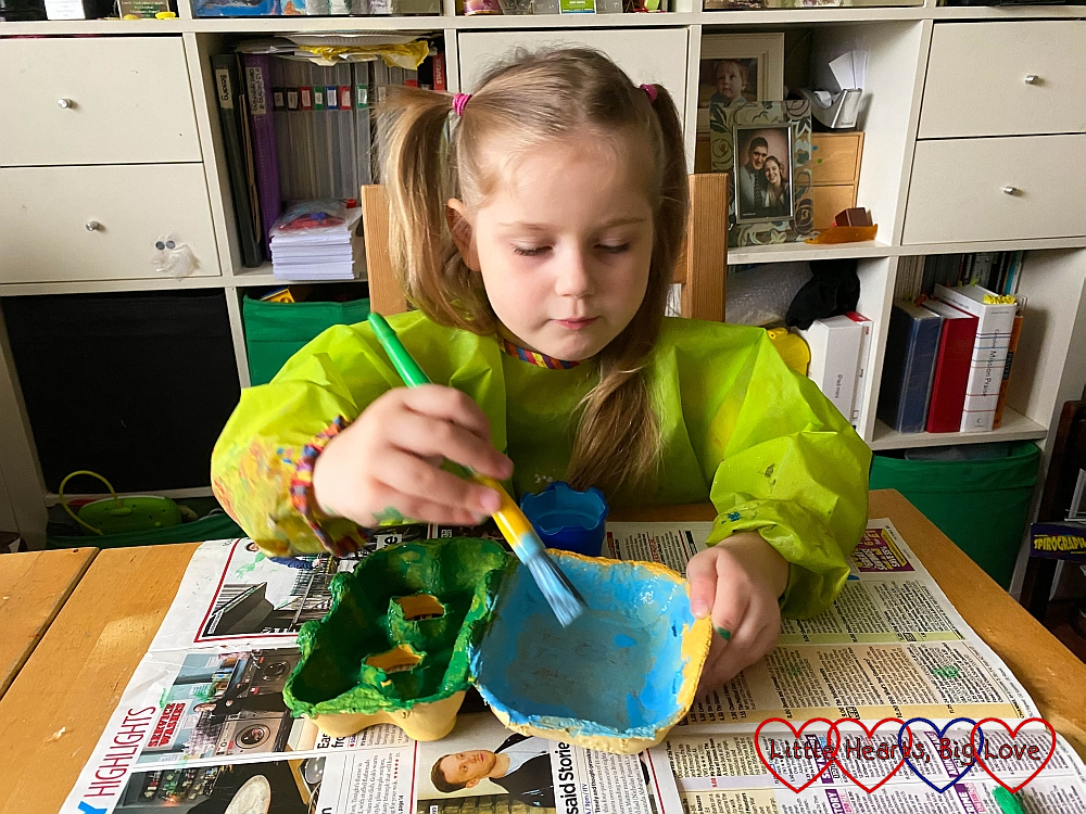 Sophie painting the inside of an egg box with blue paint