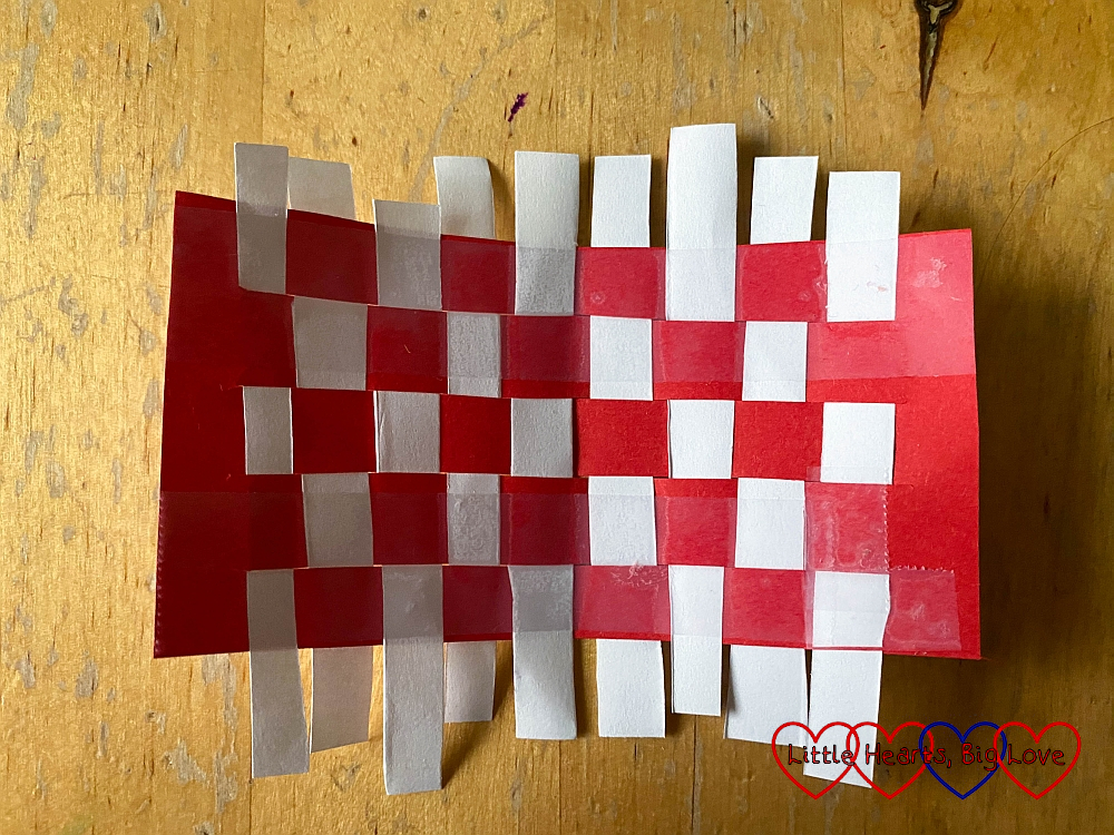 Woven strips of red and white paper to make a miniature picnic blanket