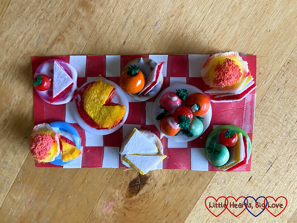 The miniature teddy bears' picnic blanket with miniature food on the button plates