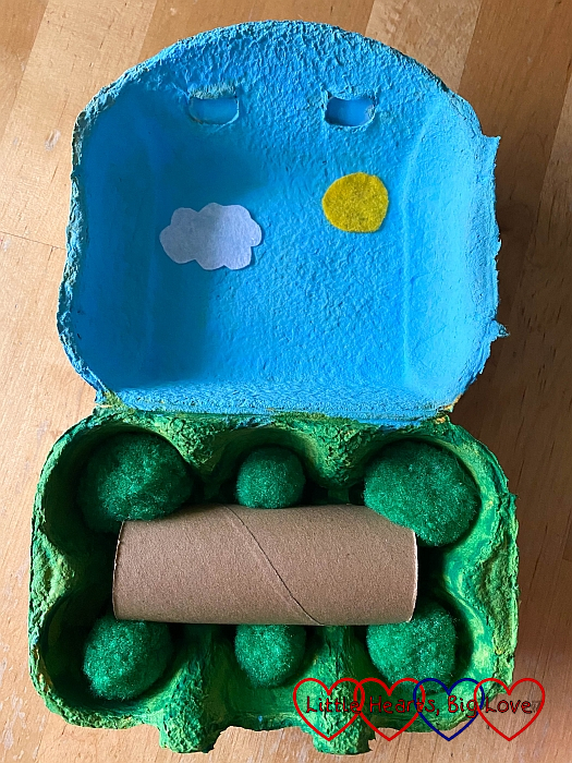 The painted egg box with green pompoms and half a toilet roll tube in the bottom half