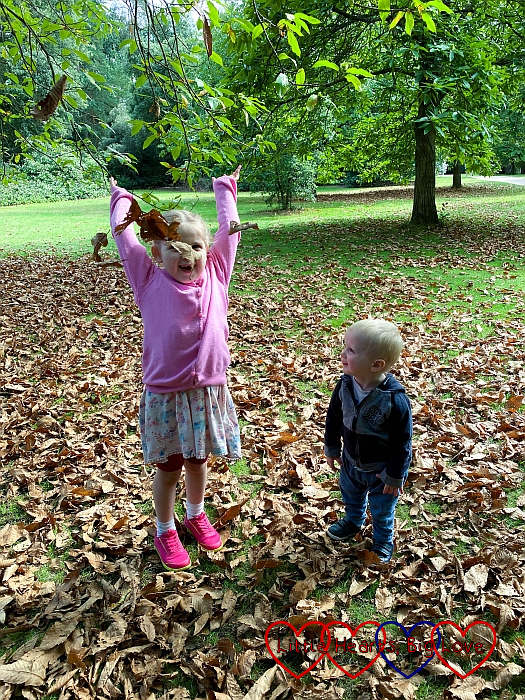 Sophie throwing autumn leaves in the air with Thomas watching