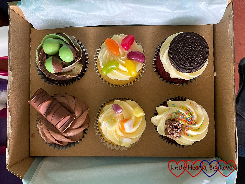 A box of six cupcakes - with different toppings (Aero mint balls, jelly beans, dolly mixtures, a flake and sprinkles, a Kinder Bueno and an Oreo cookie)