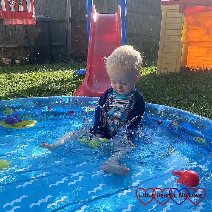 Thomas splashing in the paddling pool