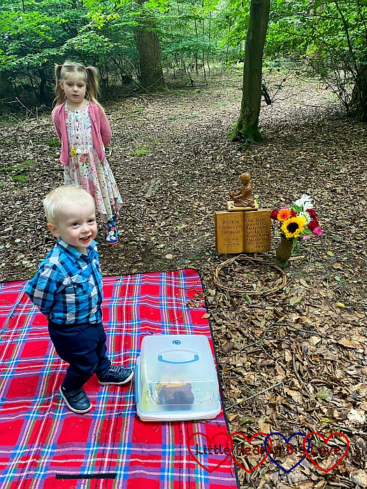 Sophie and Thomas standing on the picnic blanket by Jessica's forever bed with a cake box on the picnic blanket