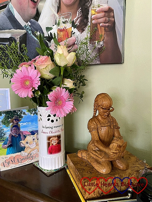 Pink gerberas and pale pink roses in Jessica's memory vase next to a wooden carving of Jessica holding her Kerry doll