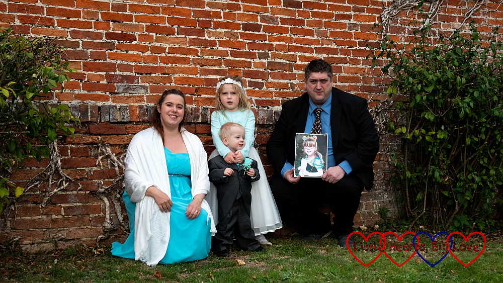 Me and Sophie in our bridesmaid dresses, Thomas in his page boy suit and hubby holding a photo of Jessica standing in front of a wall at my sister's wedding