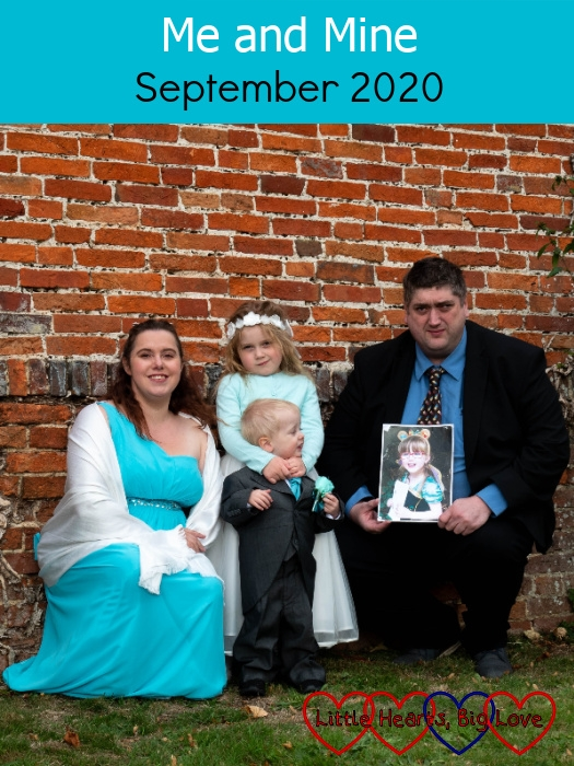 "Me and Sophie in our bridesmaid dresses, Thomas in his page boy suit and hubby holding a photo of Jessica standing in front of a wall at my sister's wedding - ""Me and Mine - September 2020"""