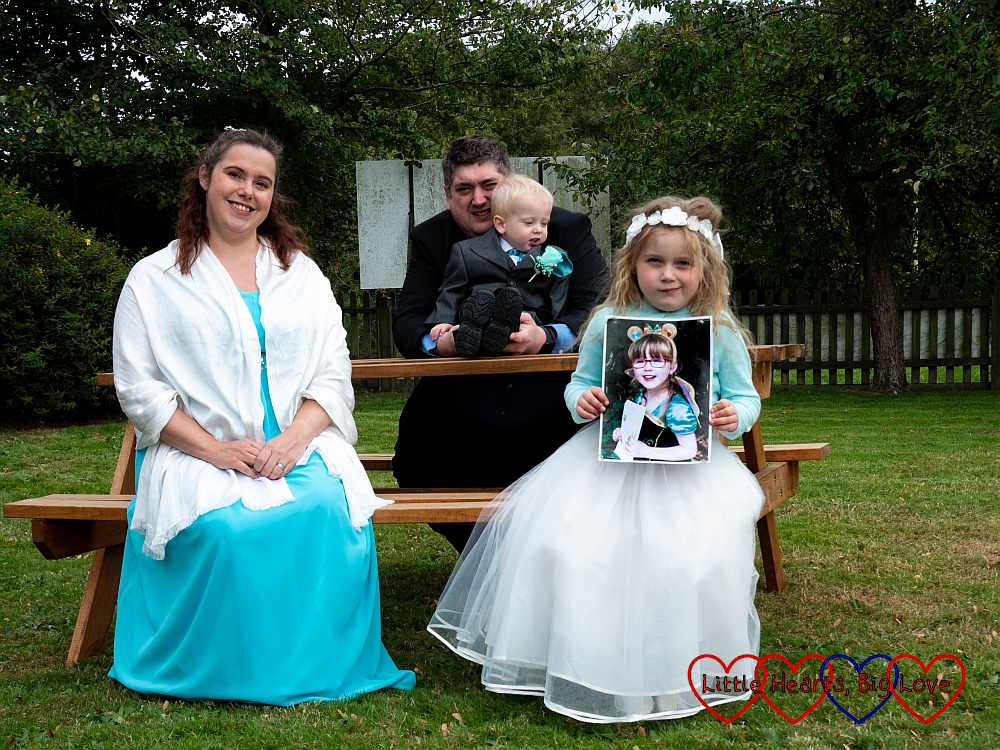 Me in my bridesmaid dress, hubby holding Thomas in his page boy suit and Sophie in her bridesmaid dress holding a picture of Jessica