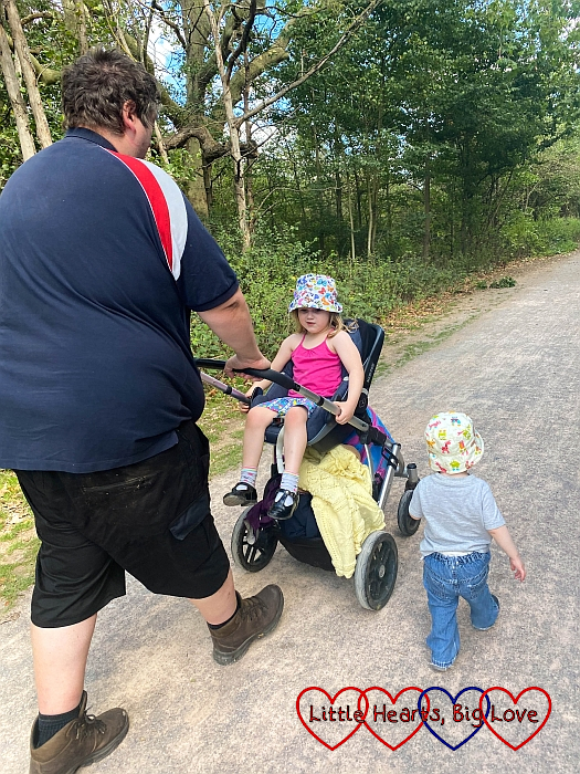 Daddy pushing the buggy with Sophie sitting inside and Thomas walking along next to them