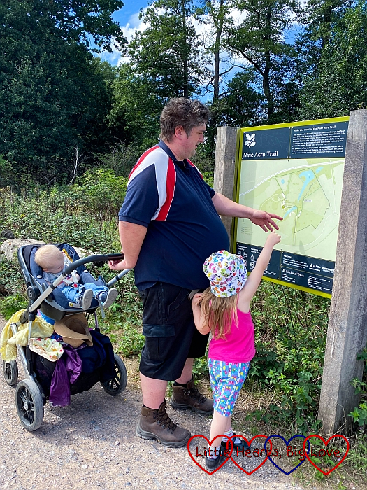 Thomas in the buggy and Daddy and Sophie looking at a map showing the Nine Acres Trail
