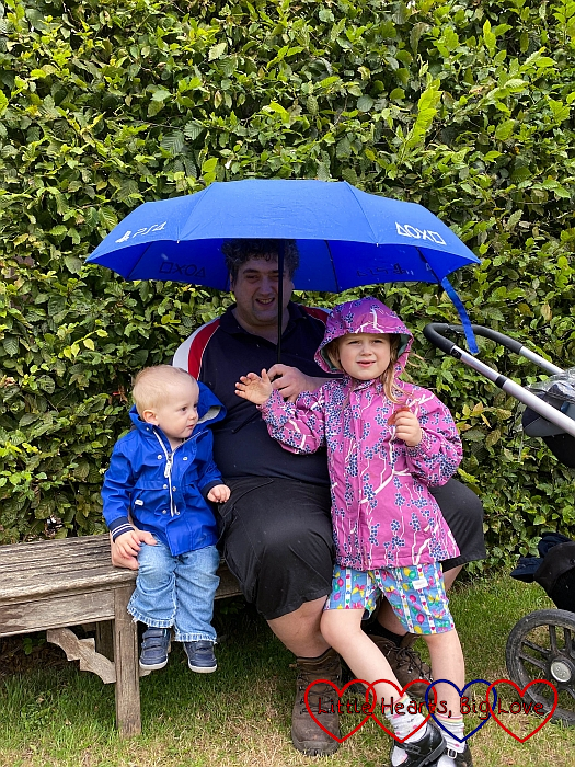Thomas, Daddy and Sophie sitting under an umbrella in the walled garden at Osterley Park