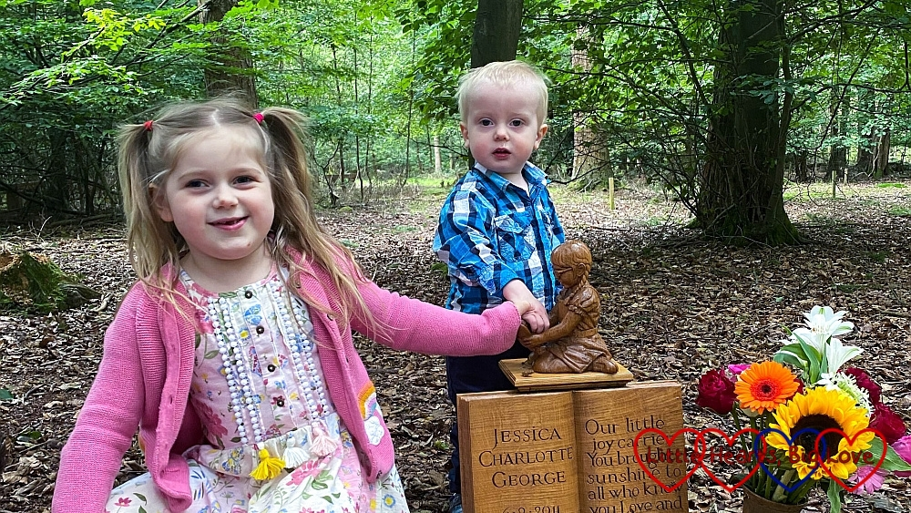 Sophie and Thomas with the wooden carving of Jessica at Jessica's forever bed