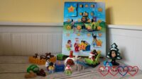 The Playmobil 1.2.3 advent calendar with a festive Playmobil scene in front showing the pieces contained within the advent calendar