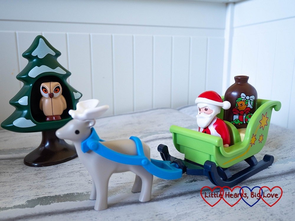 A Playmobil 1.2.3 Santa in his sleigh with a reindeer pulling the sleigh and an owl inside a snowy tree in the background