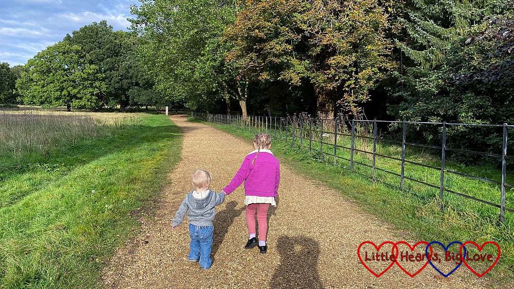 Sophie and Thomas walking hand-in-hand along a gravel path at Langley Park