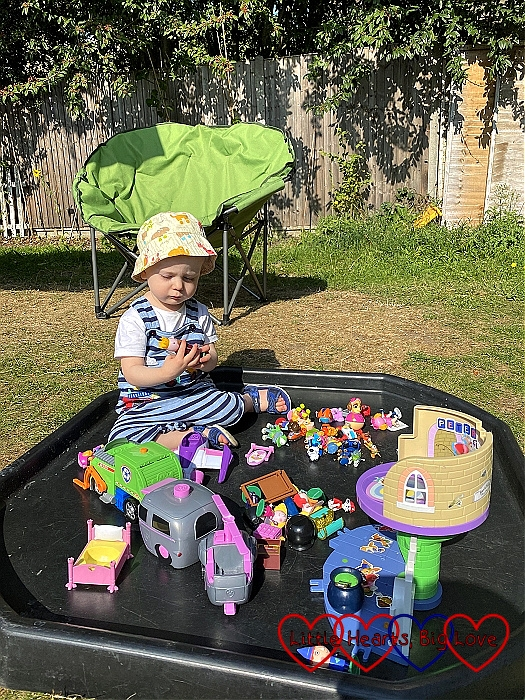Thomas sitting in the tuff tray in the sunshine playing with his toys